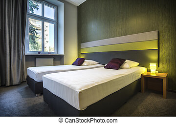 Two single beds in green hotel room - Two neat, single beds...