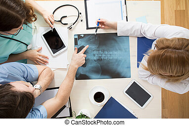 Doctors interpreting x-ray image - Doctors sitting around...