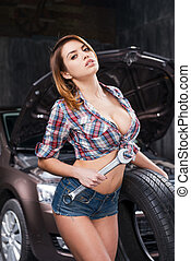 Working in repair shop Attractive young woman holding wrench...