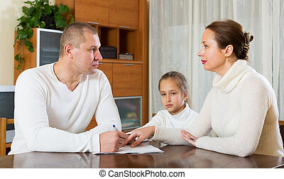Sad family of three with documents at home