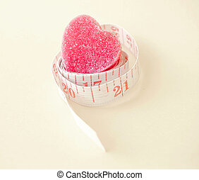 measuring tape around jelly heart (health concept)