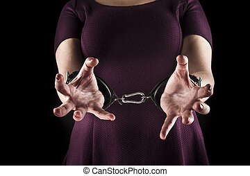 submissive woman wearing a purple dress in leather handcuffs...