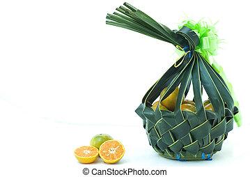 Orange fruit in wickerwork basket from a coconut leaf