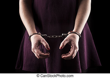 submissive woman wearing a purple dress in metal handcuffs...