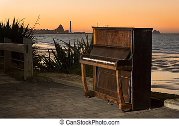 Beach Piano - Old piano on a beach walkway with the port of...
