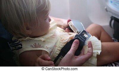 mother fastens and unfastens safety belt - mother fastens...