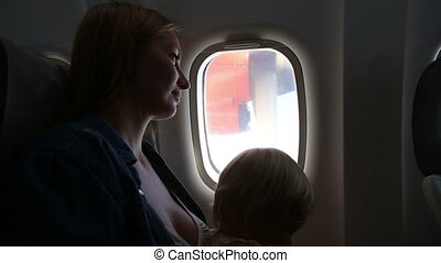 woman smile and looks out of plane window - young beautiful...