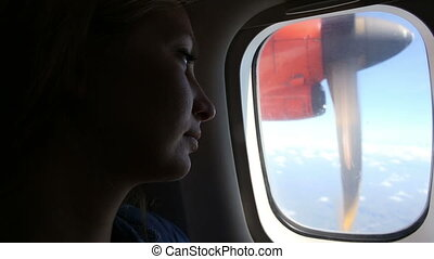 young girl looks out of plane window - young beautiful girl.