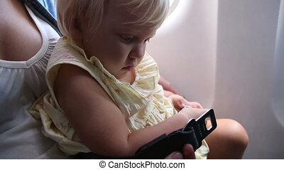 little child play with safety belt buckle in airplane -...