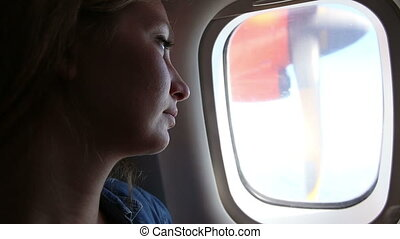 woman looks out of plane window - young beautiful woman with...