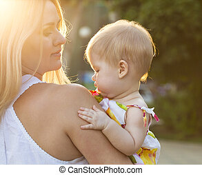 Mother and her baby enjoy the sunset - Mother and her baby...
