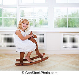 Little cute girl in nursery room with wooden horse