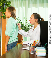 doctor with stethoscope examining teenage boy - doctor with...