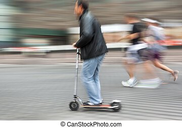 Man on a scooter and a pair running down the street