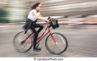 Girl cyclist in traffic on the city roadway. Intentional...