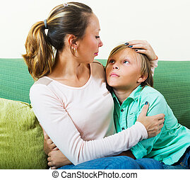 Mother consoling sad teenager at home Focus on boy
