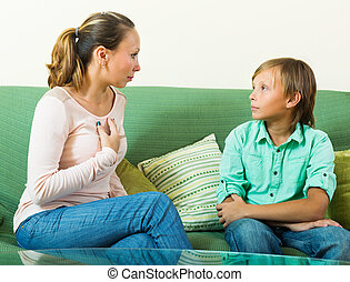 teenager son and mother having serious talking in home...