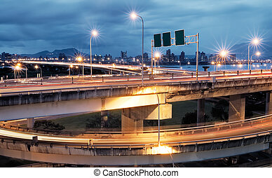 interchange with cars light - It is a cityscape of...