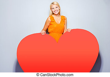 All my heart is for you. Beautiful young blond hair woman in pretty dress looking at camera holding hands on huge red heart and smiling while standing against grey background