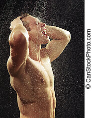 Handsome young man taking a shower - Unleashed freedom. Side...