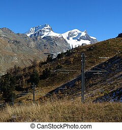 Snow capped mountains and power poles of the train to the...
