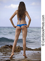 woman in bikinis on the beach, shot from behind