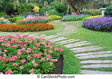 Brown chair in a flowers garden with walkway - colorful...