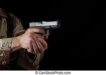 Male soldier pointing his weapon in darkness