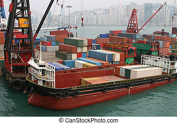 A barge being loaded with containers at a container terminal...