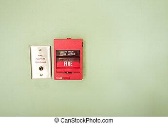 Fire break glass Fire alarm in the alarm on green wall.