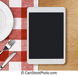 tablet pc on dinner table with plate, fork and knife