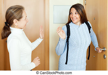 Mature woman sees off his young daughter at the door from...