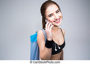 Happy sports woman talking on the phone over gray background
