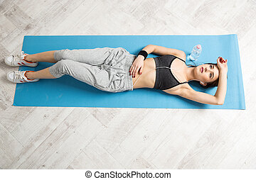 Top view portrait of a young woman lying on the yoga mat at...
