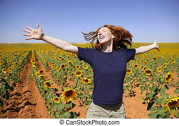 Happy redhead woman in sunflowers field outdoors