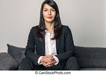 Businesswoman sitting looking at the camera - Attractive...