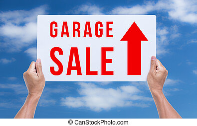 Two hands holding brown cardboard with garage sale on blue sky b