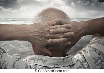 Senior man at the sea - Senior man with hands behind his...