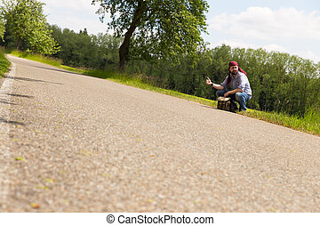 male hitchhiker is sitting on a street, holding a thumb up