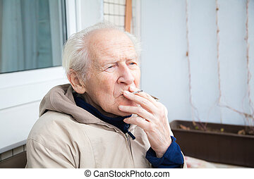 old man smoking a cigarette - thoughtful old man smoking a...