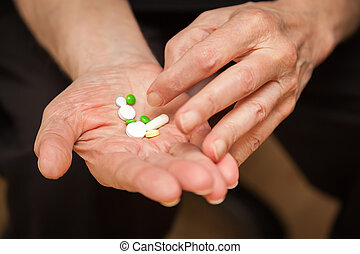 close-up old mans hands with pills, he is going to take some...