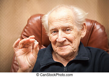old smiling man holding a tablet, he is going to take some...