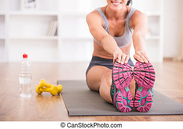 Fitness at home - Close-up of young sporty woman is siting...