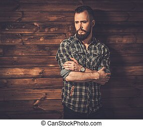 Handsome man wearing checkered shirt in wooden rural house...