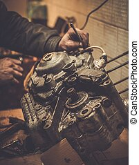 Mechanic working with with motorcycle engine in a workshop