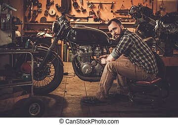Mechanic building vintage style cafe-racer motorcycle in...