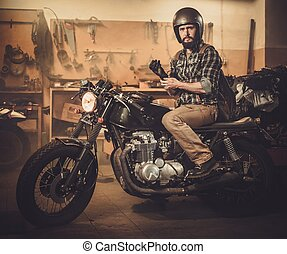 Rider and his vintage style cafe-racer motorcycle in customs...