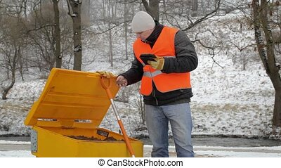 Worker with tablet PC near the sandbox in winter