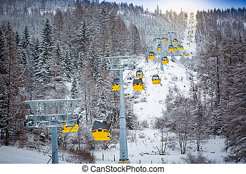 panoramic shot of long line of cable cars on ski slope -...