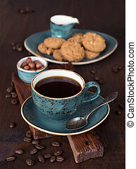 Black coffee in blue vintage cup on old dark cutting board